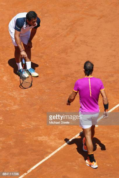 Rafael Nadal of Spain walks towards an injured Nicolas Almagro of Spain who retired whilst losing 03 in the opening set on Day Four of The...