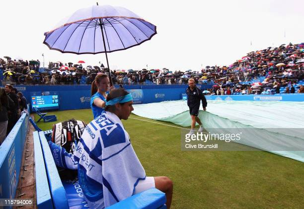 Rafael Nadal of Spain watches on from the sidelines as rain delays play during his Men's Singles quarter final match against JoWilfred Tsonga of...
