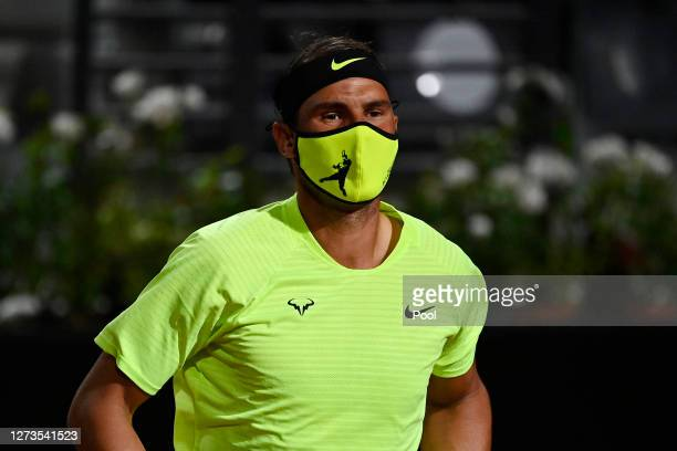 Rafael Nadal of Spain wears a face mask as he looks on prior to his quarterfinal match against Diego Schwartzman of Argentina during day six of the...