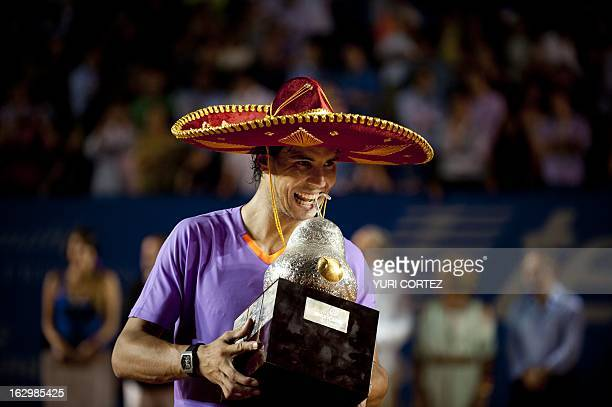Rafael Nadal of Spain wears a traditional Mexican mariachi hat while holding the winning trophy after defeating his compatriot David Ferrer at the...