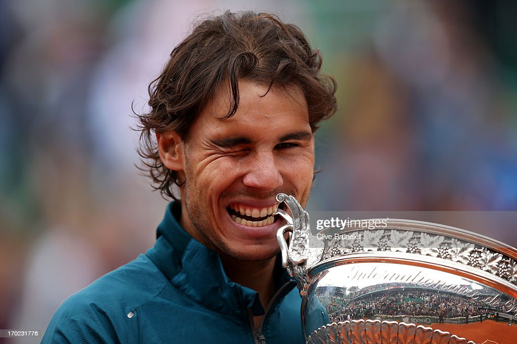 Rafael Nadal of Spain winks as hecelebrates and bites the Coupe des Mousquetaires trophy in the men's singles final against David Ferrer of Spain during day fifteen of the French Open at Roland Garros on June 9, 2013 in Paris, France.