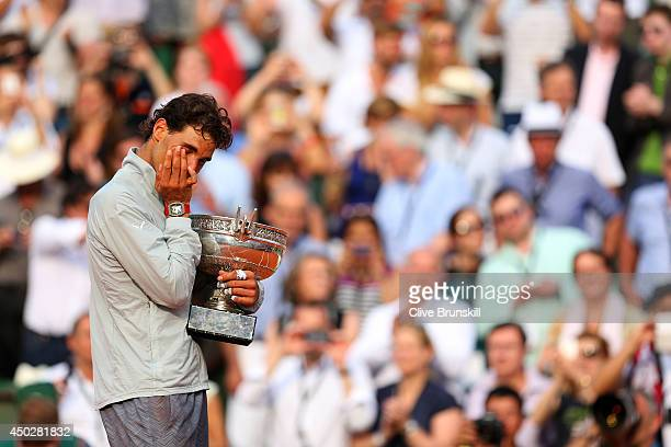 Rafael Nadal of Spain wipes tears away from his eyes as he celebrates with the Coupe de Mousquetaires after victory in his men's singles final match...