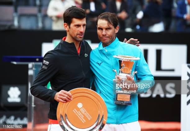 Rafael Nadal of Spain with his winners trophy and Novak Djokovic of Serbia with his runners up trophy after Nadal's three set victory in the men's...