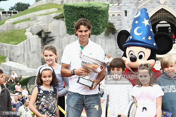 Rafael Nadal poses with the winner of the Men's Singles cup named 'La Coupe des Mousquetaires' after winning his sixth victory at the French Open at...