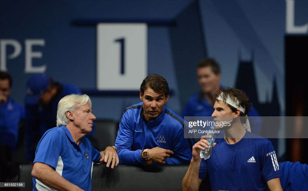 Rafael Nadal talks with Bjorn Borg, Captain of Team Europe and Austrian Dominic Thiem during the match between Dominic Thiem and John Isner of United States and Team World during the first day of the Laver Cup on September 22, 2017 at the O2 Arena, in Prague. / AFP PHOTO / Michal Cizek