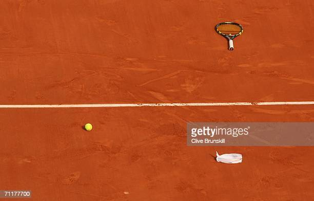 Rafael Nadal's racquet sweatband and a ball lie on the clay after he defeated Roger Federer of Switzerland during the Men's Singles Final on day...