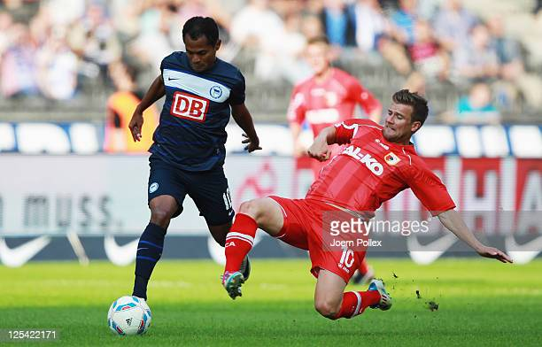 Rafael of Berlin and Daniel Baier of Augsburg battle for the ball during the Bundesliga match between Hertha BSC Berlin and FC Augsburg at Olympic...