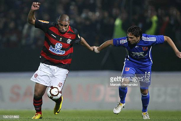 Rafael Olarra of Universidad de Chile fights for the ball with Adriano of Flamengo during a match as part of the Libertadores Cup 2010 at Santa Laura...