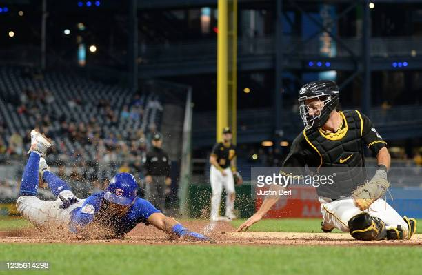 Rafael Ortega of the Chicago Cubs steals home plate ahead of a tag attempt by Jacob Stallings of the Pittsburgh Pirates in the second inning during...