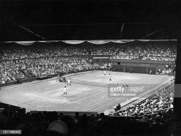 Rafael Osuna and Antonio Palafox of Mexico play a forehand return to Jean-Claude Barclay and Pierre Darmon of France during their Men's Doubles Final...