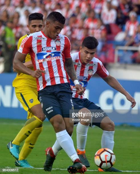 Rafael Perez and Jorge Arias de la Hoz of Junior vie for the ball with Emanuel Reynoso of Boca Juniors during a Copa CONMEBOL Libertadores match...