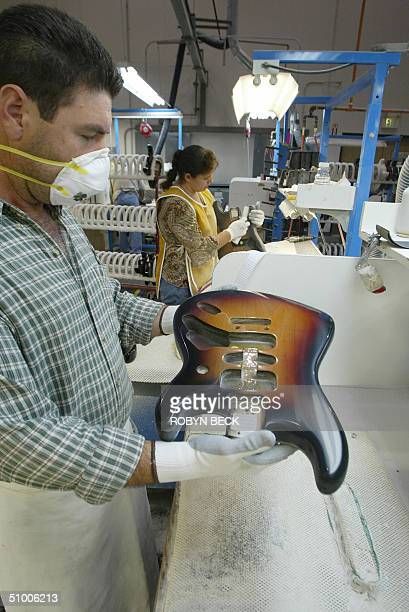 Rafael Ramos examines a Stratocaster body he is buffing after painting at the Fender manufacturing facility in Corona California 28 June 2004 The...