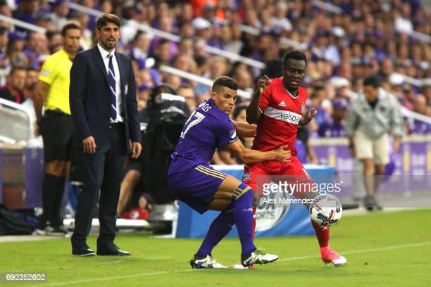 ORLANDO FL JUNE 4 Rafael Ramos of Orlando City SC grabs David Accam of Chicago Fire as Fire head coach Veljko Paunovic looks on during a MLS soccer...