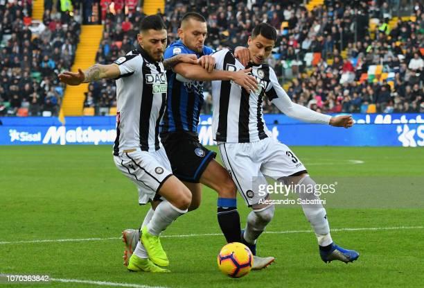 Rafael Toloi of Atalanta BC competes for the ball with Giuseppe Pezzella of Udinese Calcio and Rolando Mandragora of Udinese Calcio during the Serie...