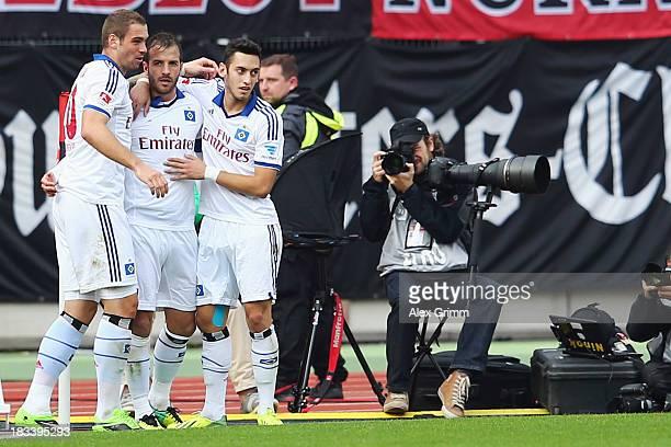 Rafael van der Vaart of Hamburg celebrates his team's first goal with team mates PierreMichel Lasogga and Hakan Calhanoglu during the Bundesliga...