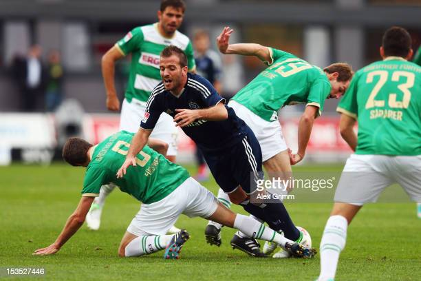 Rafael van der Vaart of Hamburg is challenged by Stefan Fuerstner Thomas Kleine and Sercan Sararer of Greuther Fuerth during the Bundesliga match...