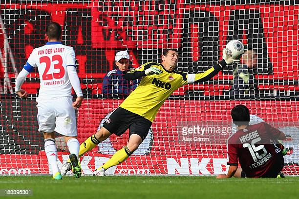 Rafael van der Vaart of Hamburg scores his team's first goal against goalkeeper Raphael Schaefer and Makoto Hasebe of Nuernberg during the Bundesliga...