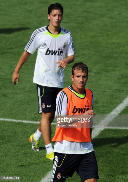 Rafael van der Vaart of Real Madrid watches on besides new signing Mesut Ozil during a training session at the Valdebebas training ground on August...