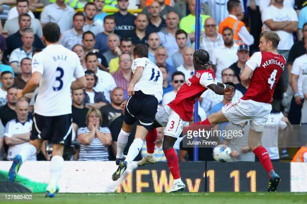 Rafael Van der Vaart of Tottenham Hotspur scores the opening goal past the challenges of Bacary Sagna and Per Mertesacker of Arsenal during the...