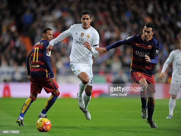 Rafael Varane of Real Madrid is tackled by Sergio Busquets of FC Barcelona during the La Liga match between Real Madrid and Barcelona at Estadio...