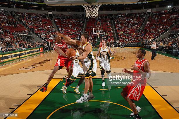 Rafer Alston of the Houston Rockets tries to pass the ball to teammate Tracy McGrady of the Rockets under pressure from Wally Szczerbiak of the...