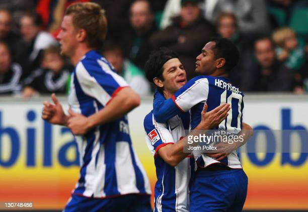 Raffael celebrates with bis team mate Levan Kobiashvili after scoring his team's first goal of Berlin battle for the ball during the Bundesliga match...