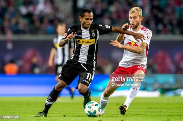 Raffael of Borussia Moenchengladbach and Konrad Laimer of RB Leipzig battle for the ball during the Bundesliga match between RB Leipzig and Borussia...