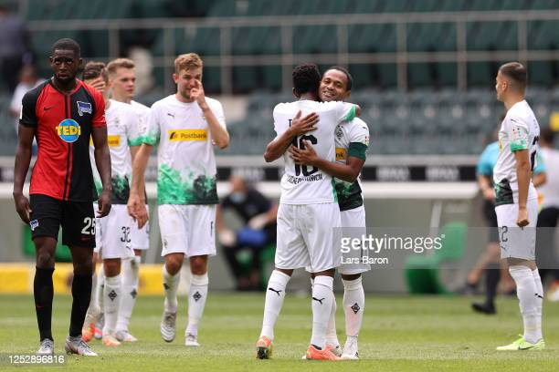 Raffael of Borussia Moenchengladbach embraces Ibrahima Traore of Borussia Moenchengladbach following their victory in the Bundesliga match between...
