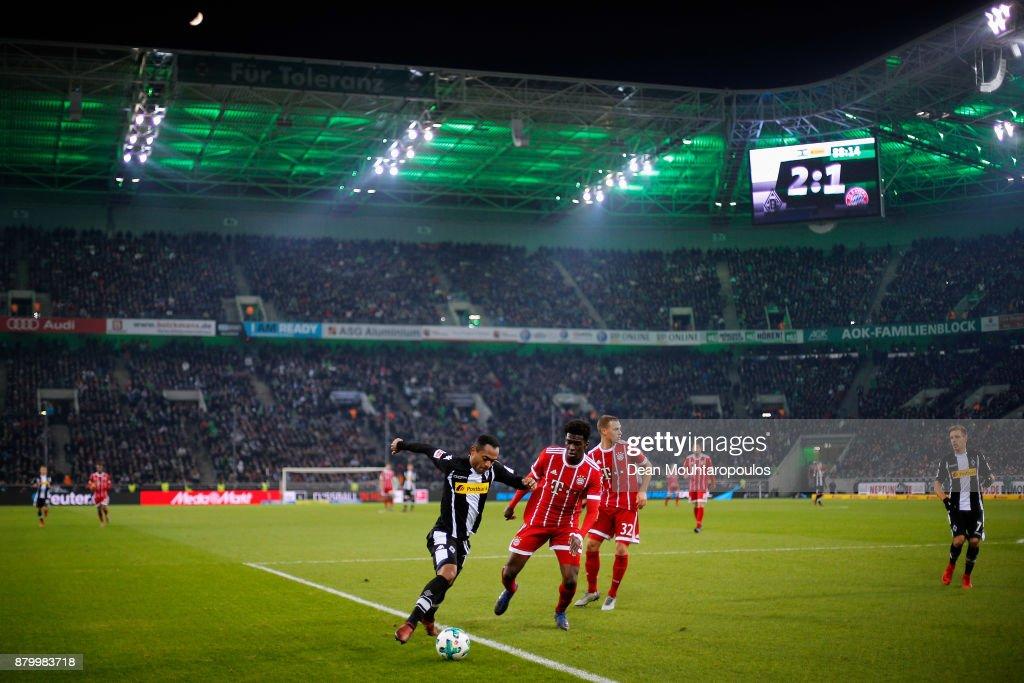 Raffael of Borussia Monchengladbach battles for the ball with Kwasi Okyere Wriedt of Bayern Munich during the Bundesliga match between Borussia Moenchengladbach and FC Bayern Muenchen at Borussia-Park on November 25, 2017 in Moenchengladbach, Germany.