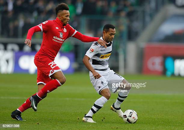 Raffael of Moenchengladbach and JeanPhilippe Gbamin of Mainz battle for the ball during the Bundesliga match between Borussia Moenchengladbach and...