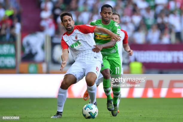 Raffael of Moenchengladbach fights for the ball with Rani Khedira of Augsburg during the Bundesliga match between FC Augsburg and Borussia...