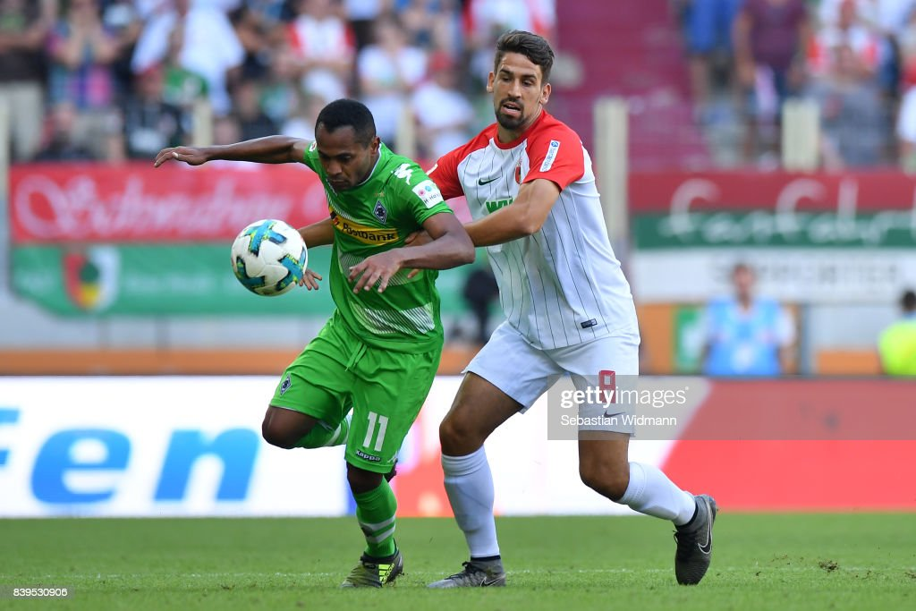 Raffael of Moenchengladbach (l) fights for the ball with Rani Khedira of Augsburg during the Bundesliga match between FC Augsburg and Borussia Moenchengladbach at WWK-Arena on August 26, 2017 in Augsburg, Germany.