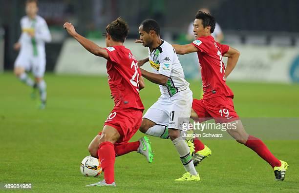 Raffael of Moenchengladbach tackles JeongHo Hong of Augsburg and JaCheol Koo during the Bundesliga match between Borussia Moenchengladbach and FC...