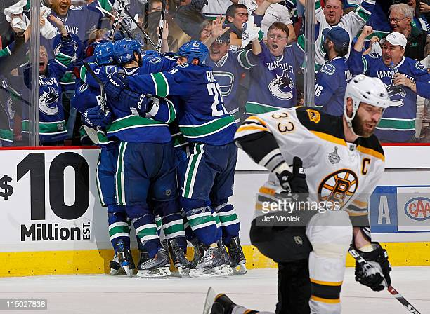 Raffi Torres of the Vancouver Canucks celebrates his game winning third period goal with teammates while Zdeno Chara of the Boston Bruins looks on in...