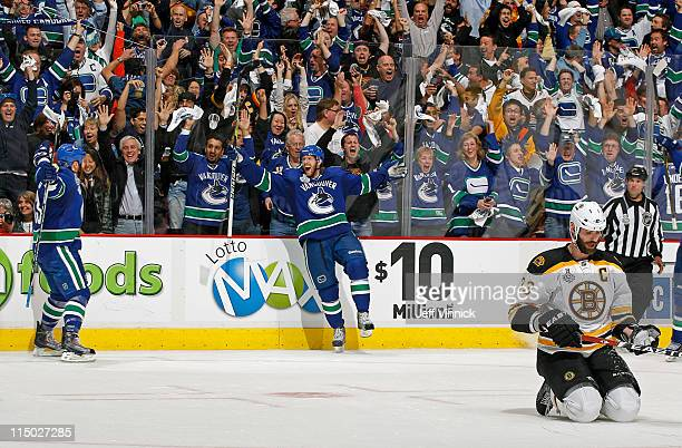 Raffi Torres of the Vancouver Canucks celebrates his third period game winning goal with teammate Jannik Hansen of the Vancouver Canucks while Zdeno...