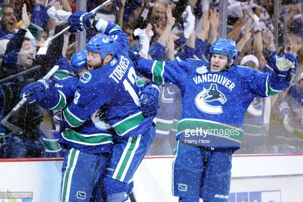 Raffi Torres of the Vancouver Canucks celebrates with his teammates Victor Oreskovich and Kevin Bieksa after a goal late in the third period against...