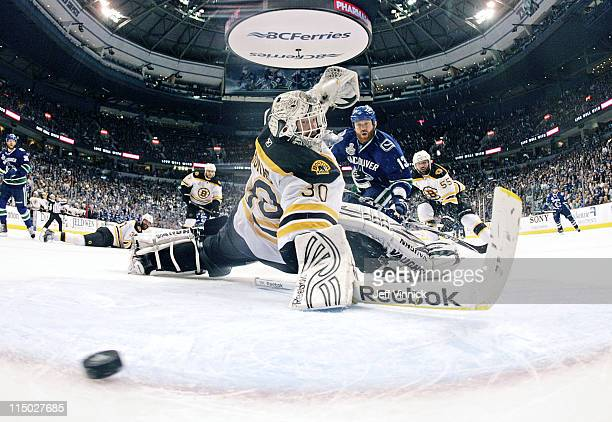 Raffi Torres of the Vancouver Canucks scores with 18 seconds left to go while Tim Thomas of the Boston Bruins looks on in Game One of 2011 NHL...
