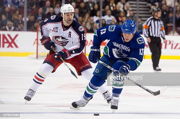 Raffi Torres of the Vancouver Canucks skates after a loose puck while being chased down by Ethan Moreau of the Columbus Blue Jackets during the...