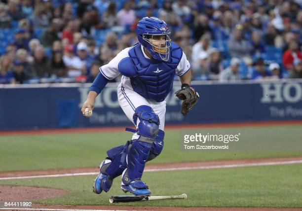 Raffy Lopez of the Toronto Blue Jays fields a soft grounder while avoiding stepping on the bat as he makes the play and throws out the baserunner in...