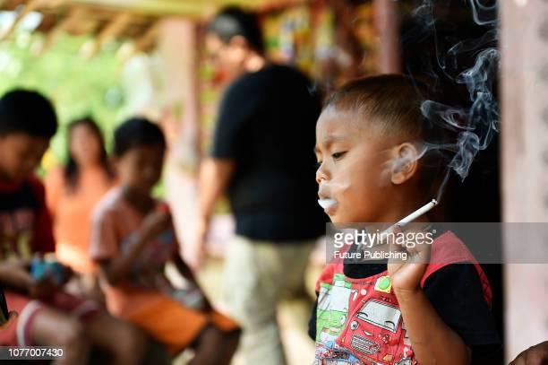 Rafi Ananda Pamungkas 25 years smoking cigarettes in front of his house in Tenjojaya village Cibadak Sukabumi West Java Indonesia Rafi is addicted to...