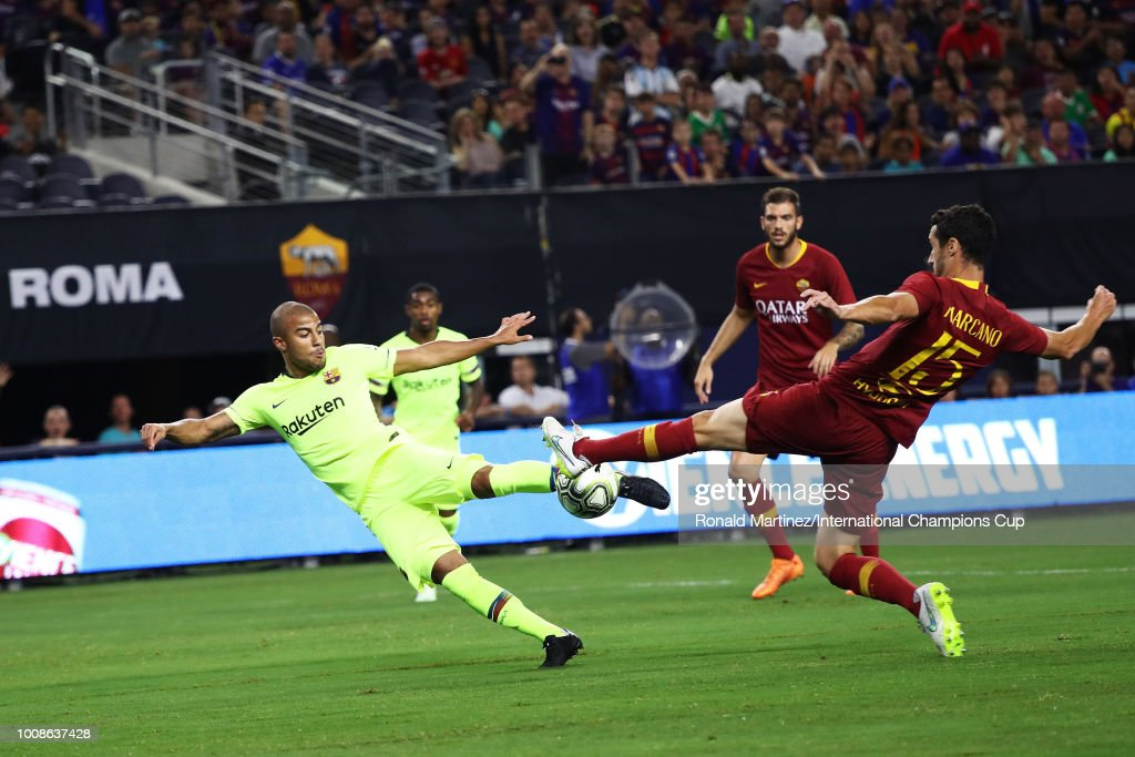 Rafinha Alcantara #12 of FC Barcelona scores a goal as Ivan Marcano #15 of AS Roma defends during their International Champions Cup 2018 match at AT&T Stadium on July 31, 2018 in Arlington, Texas.