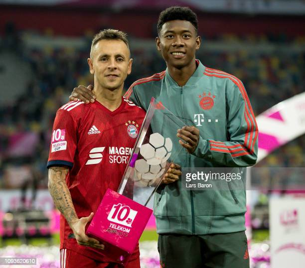 Rafinha and David Alaba of Muenchen are seen with the trophy after winning the Telekom Cup 2019 Final between FC Bayern Muenchen and Borussia...