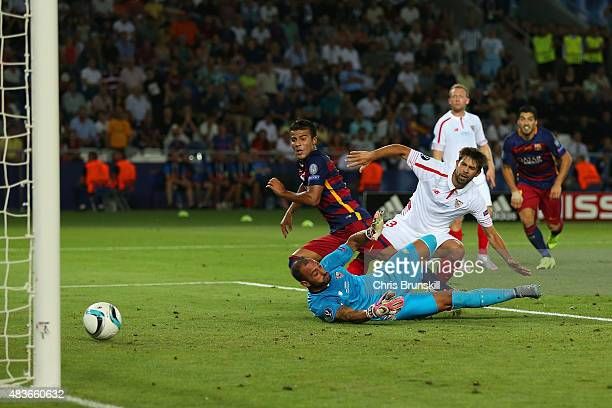 Rafinha of Barcelona scores the third goal under pressure from Beto and Coke of Sevilla during the UEFA Super Cup between Barcelona and Sevilla FC at...