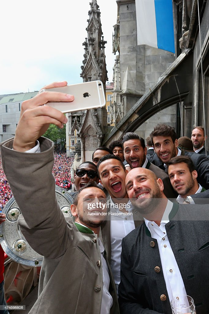 Rafinha (L) of Bayern Muenchen and his team mates (L-R) David Alaba, Medhi Benatia, Tiago, Dante, Pepe Reina, Claudio Pizarro, Javier Martinez and Juan Bernat as the team celebrate winning the German Championship title on the town hall balcony at Marienplatz on May 24, 2015 in Munich, Germany.