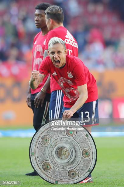 Rafinha of Bayern Muenchen celebrates with a replica of the champions trophy after Munechen won the 6th championship back to back after the...