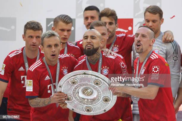 Rafinha of Bayern Muenchen lifts with his team mates Arturo Vidal and Franck Ribery the trophy in Celebration for winning the German Champiosnhip...