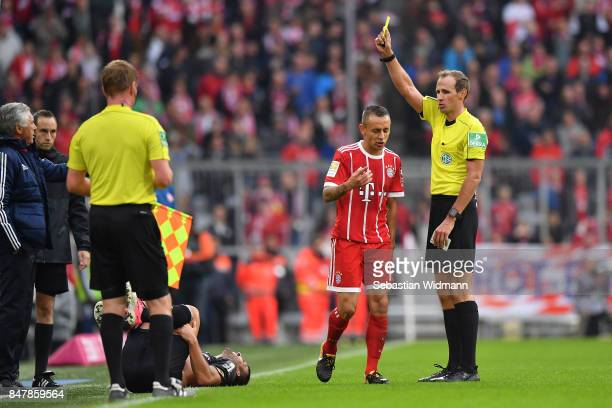 Rafinha of Bayern Muenchen receives a yellow card from referee Sascha Stegemann after a foul on Giulio Donati of Mainz during the Bundesliga match...