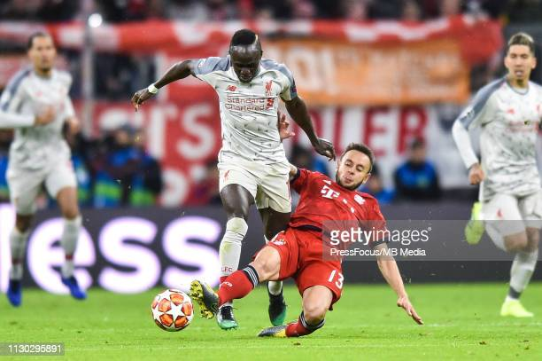 Rafinha of Bayern Muenchen tackles Sadio Mane of Liverpool during the UEFA Champions League Round of 16 Second Leg match between FC Bayern Muenchen...