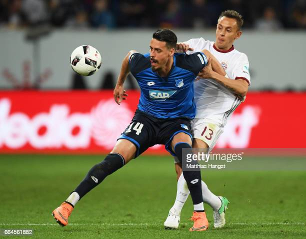 Rafinha of Bayern Munich challenges Sandro Wagner of 1899 Hoffenheim during the Bundesliga match between TSG 1899 Hoffenheim and Bayern Muenchen at...