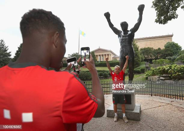Rafinha of FC Bayern Muenchen poses as his teammate David Alaba makes a photograph in front of the 'Rocky' statue next to the Philadelphia Museum of...